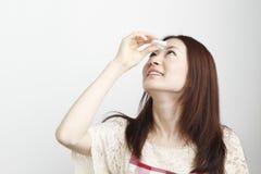 Eye drops. Young woman applying eye drops. Asian women stock photos
