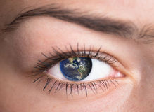 Eye with the earth inside. Stock Photos