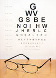 Eye Exam. An eye exam chart is blurred in the background of a pair of modern eye glasses Stock Image