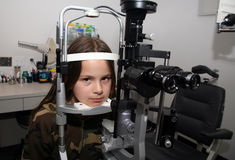 Eye exam. Young girl anxiously waiting for her eye exam Royalty Free Stock Photos
