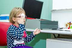 Eye exam, cute little girl is reviewing eyesight. Royalty Free Stock Photography