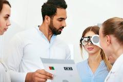 Eye Exam. Doctors Checking Woman Eyesight With Optometry Glasses royalty free stock photo