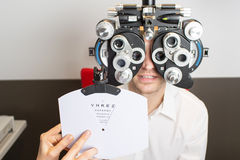 Eye exam. Man during an eye exam with thumb up royalty free stock photo
