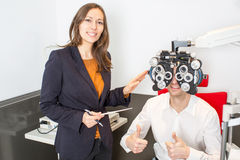Eye exam. Man during an eye exam with thumb up Royalty Free Stock Photography