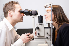 Eye exam at optician. Woman during an eye exam stock photos