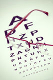 Eye Exam. A pair of black reading glasses on top of an eye test chartn stock photo