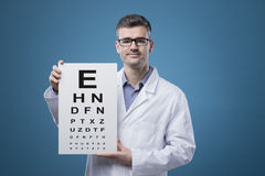 Eye exam. Professional optician holding an eye exam chart with letters stock photos