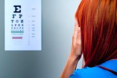 Eye examination. Young woman examines her eyes Stock Photos
