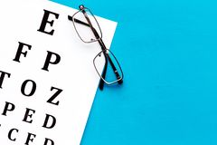 Eye examination. Eyesight test chart and glasses on blue background top view space for text stock photo
