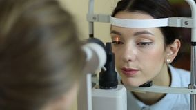 Eye examination at slit lamp in oculist office stock footage