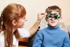 Eye examinations at ophthalmology clinic. Optometry concept. female doctor ophthalmologist or optometrist helps young boy with phoropter during sight testing or royalty free stock images