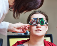 Eye examinations at ophthalmology clinic. Optometry concept. female doctor ophthalmologist or optometrist helps young woman with phoropter during sight testing royalty free stock photography
