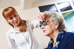 Eye examinations at ophthalmology clinic. Optometry. female doctor ophthalmologist or optometrist examines senior women eye sight with phoropter in clinic Stock Photo