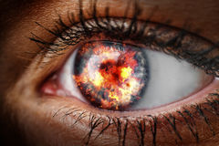 Eye with fire. Closeup of the eye of a woman with fire royalty free stock photography