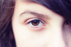 Eye of a girl. Close up view of the eye of a young girl stock images