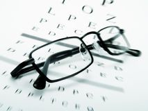 Eye glasses. On an optometrist chart Royalty Free Stock Image