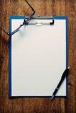 Eye-glasses and a black pen on an empty white page Stock Images