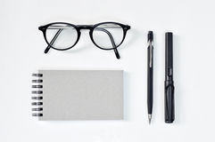 Eye glasses, blank notepad, pen, and mechanical pencil Royalty Free Stock Image
