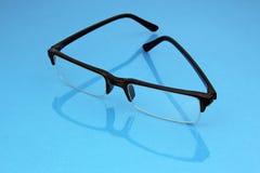 Eye glasses on blue background Royalty Free Stock Photos