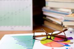 Eye glasses on the book. Business man put his eye glasses on the book chart and graph relax time after executive meeting marketing analysis royalty free stock images