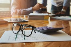 Eye glasses and calculator on report paper Royalty Free Stock Photos