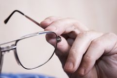 Eye-glasses in close up. Glasses in hand Stock Images