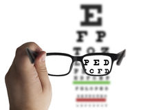 Eye glasses on eyesight test chart Stock Image