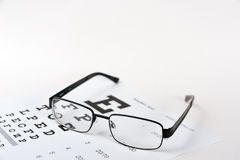 Eye glasses on eyesight test chart background Stock Images