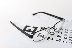 Eye glasses on eyesight test chart background stock image