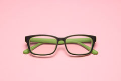 Eye glasses. Green eye glasses on pink paper background Stock Photography