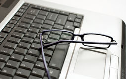 Eye glasses on laptop. Visual glasses slightly closed on a computer laptop Royalty Free Stock Image
