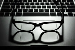 Eye glasses on laptop computer low key light. Black eye glasses with shadow on laptop computer with keyboard in background low key light Stock Images