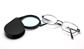 Eye glasses and magnifying glass isolated on white Stock Photos