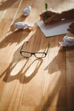 Eye glasses by man writing at desk in office Stock Photography