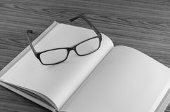 Eye glasses on note book black and white Royalty Free Stock Images