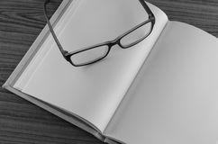 Eye glasses on note book black and white Stock Photos