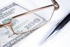 Eye-glasses, pen and banknote Stock Photo