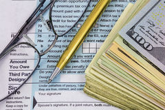 Eye glasses pen cash tax form money management. The pile stash stack of cash paper American USA currency payment for federal income taxes for Internal Revenue stock photography