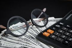 Eye glasses on pile of dollar banknotes and calculator with blac Royalty Free Stock Photo