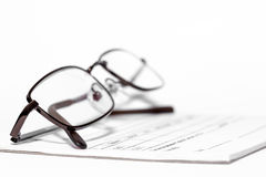 Eye glasses on prescription pad. Eye glasses resting on a prescription pad used for writing out eye glasses prescriptions all  isolated on a white background Royalty Free Stock Photo