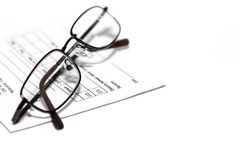 Eye glasses on prescription pad. Eye glasses resting on a prescription pad used for writing out eye glasses prescriptions all  isolated on a white background Stock Photo