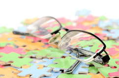Eye glasses and puzzle Stock Photos