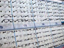 Eye glasses in racks for sale in an opticians. Stock Image