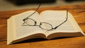 Eye glasses resting on top of a book, sitting on a wooden coffee table stock images