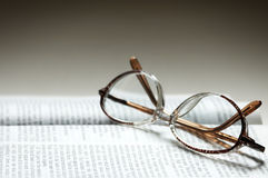 Eye-glasses on the text. Glasses and book (special photo f/x,focus point on the nearest part of the glasses Stock Photography