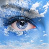 Eye of the God. Blue human eye and cloudy sky on face Royalty Free Stock Photos