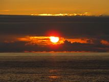 The eye of God. Sunset through the clouds sighted from the shore royalty free stock photo