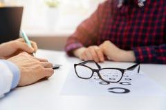 Eye health - black glasses on eyesight test chart in optician office. Close up stock image