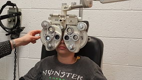Eye healthcare. A  Caucasian  boy at the optometrists having an eye test Stock Photos