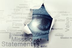 Eye in a hole of torn paper. Eye watching from the hole of torn paper sheet with business keywords collage royalty free stock images